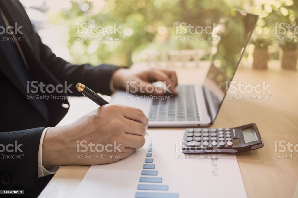 Close up shot of a businessman writing on charts paper at workstation. Modern business man writing on chart paper and using laptop computer. Business concept, Marketing plan, Successful Business. stock photo
