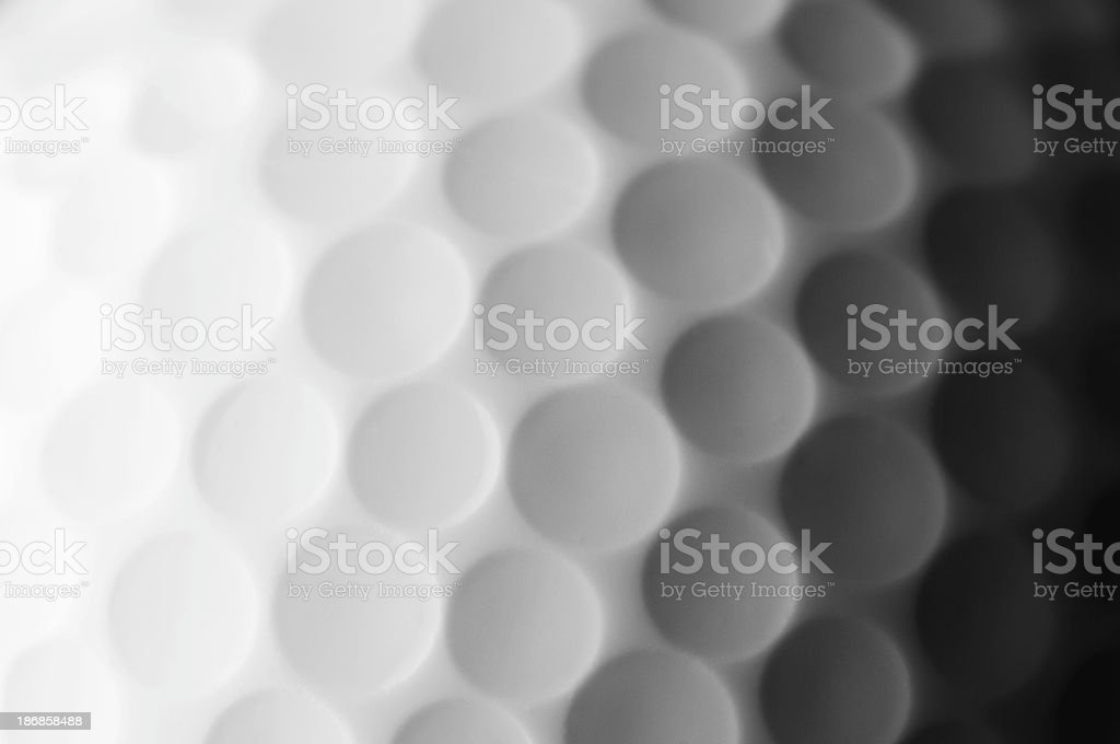 A close up shot of a golf ball, white and fade to dark gray stock photo