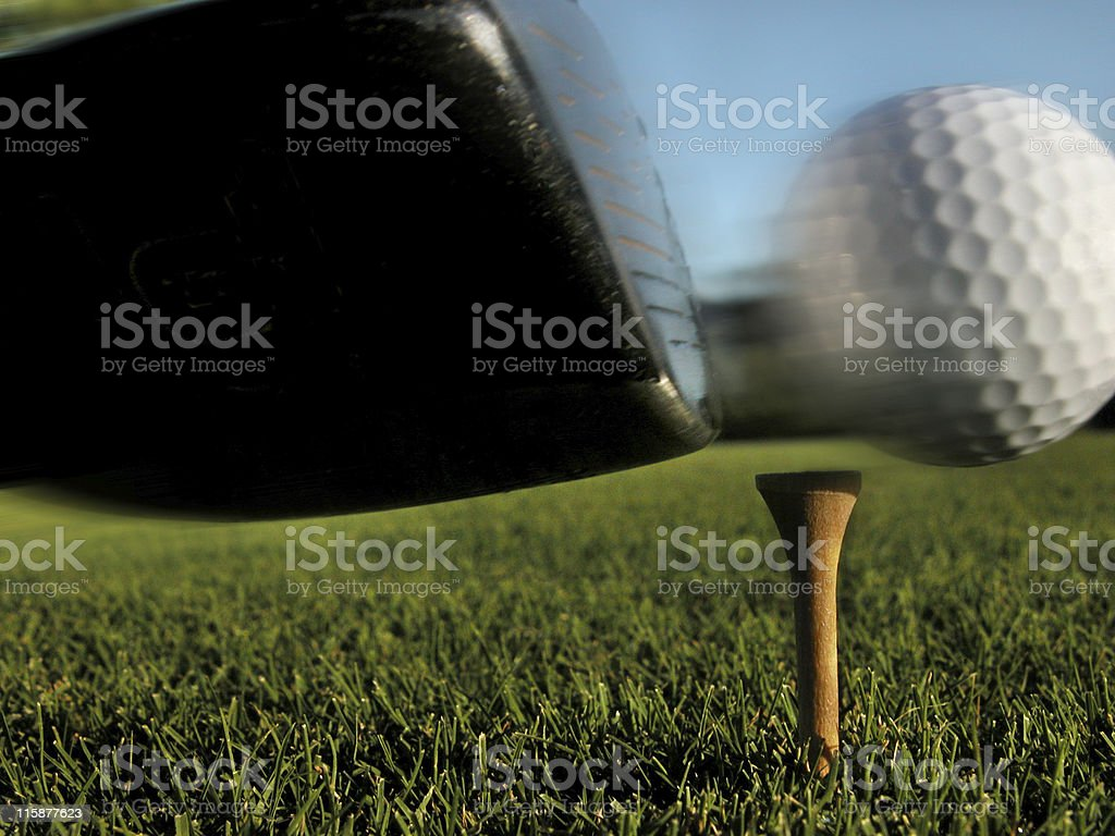 A close up shot of a golf club hitting the ball at the tee stock photo