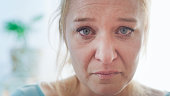 istock Close up shot of a portrait of a mid adult woman crying while looking at camera. Woman in pain and grief 1223595213
