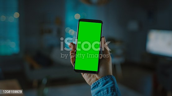 Close Up Shot of a Smartphone with Green Screen Great for Mock-up. Person is Holding Phone and Giving a Voice Command to Switch on the Light on the Backgroung in Living Room.
