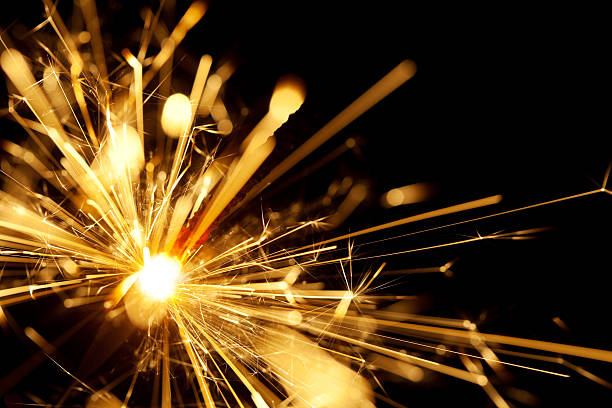 A close up shot of a yellow sparkler with black background  stock photo
