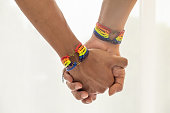 Close up shot of Asian Male couple holding hands with  gay pride rainbow awareness wristbands. LGBT, same-sex love and homosexual relationships with copy space.