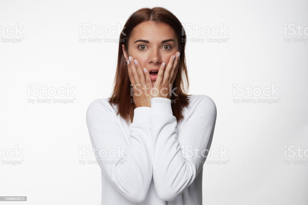 b5d1fb76edb1 Close up foto de mujer joven atractiva con expresión aturdida, toca las  mejillas con ambas