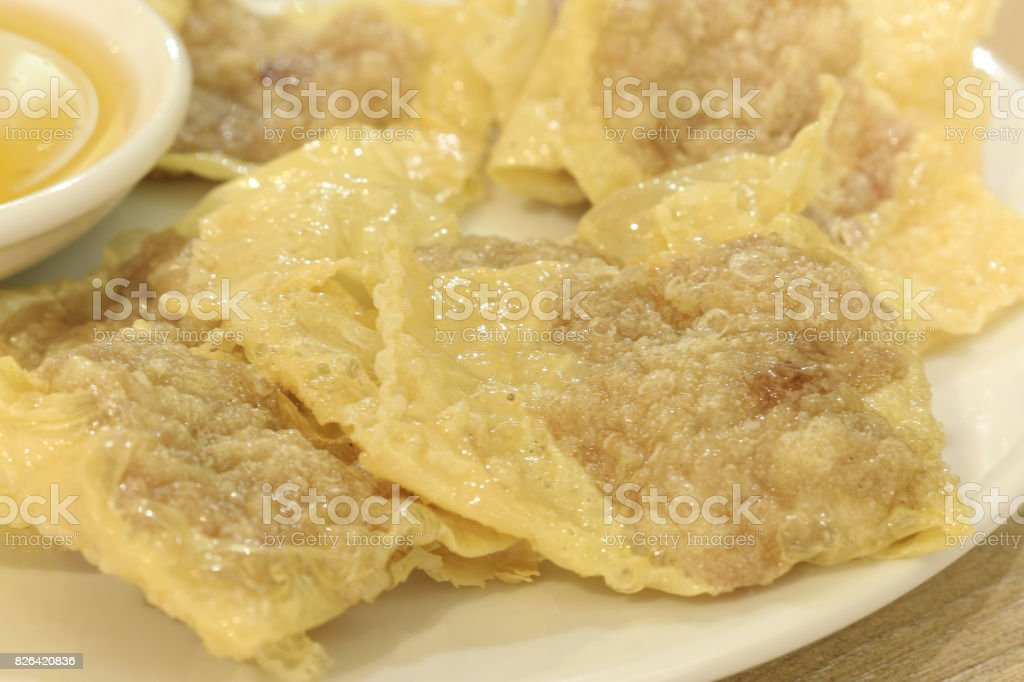 close up shot of bean curd skin pork roll with plum sauce on white dish and wood table stock photo