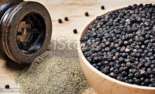 Black peppercorns and milled pepper, arrangement in a wooden bowl. Close up shot of black pepper, cooking ingredient scene and wooden table. Top view.