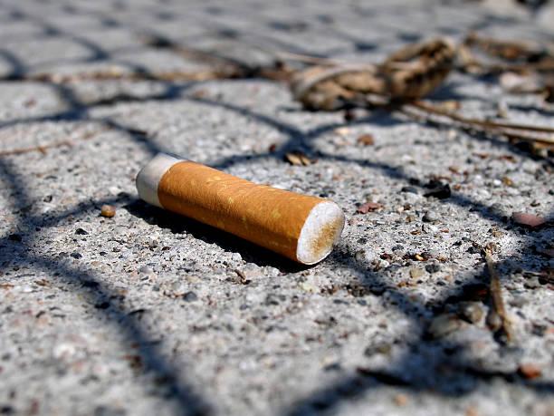 close-up shot di filtro di sigaretta sul marciapiede - cicca sigaretta foto e immagini stock