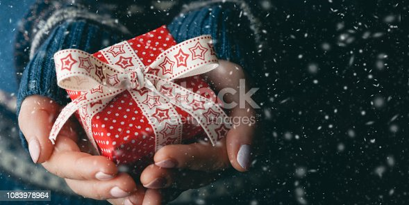 Close up shot of female hands holding a small gift. Shallow depth of field with focus on the little box.