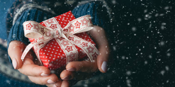close up shot of female hands holding a small gift - regalo natale foto e immagini stock