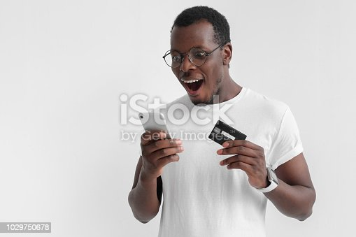istock Close up shot of handsome african american man standing isolated on gray background, holding smartphone in one hand and credit card in another 1029750678