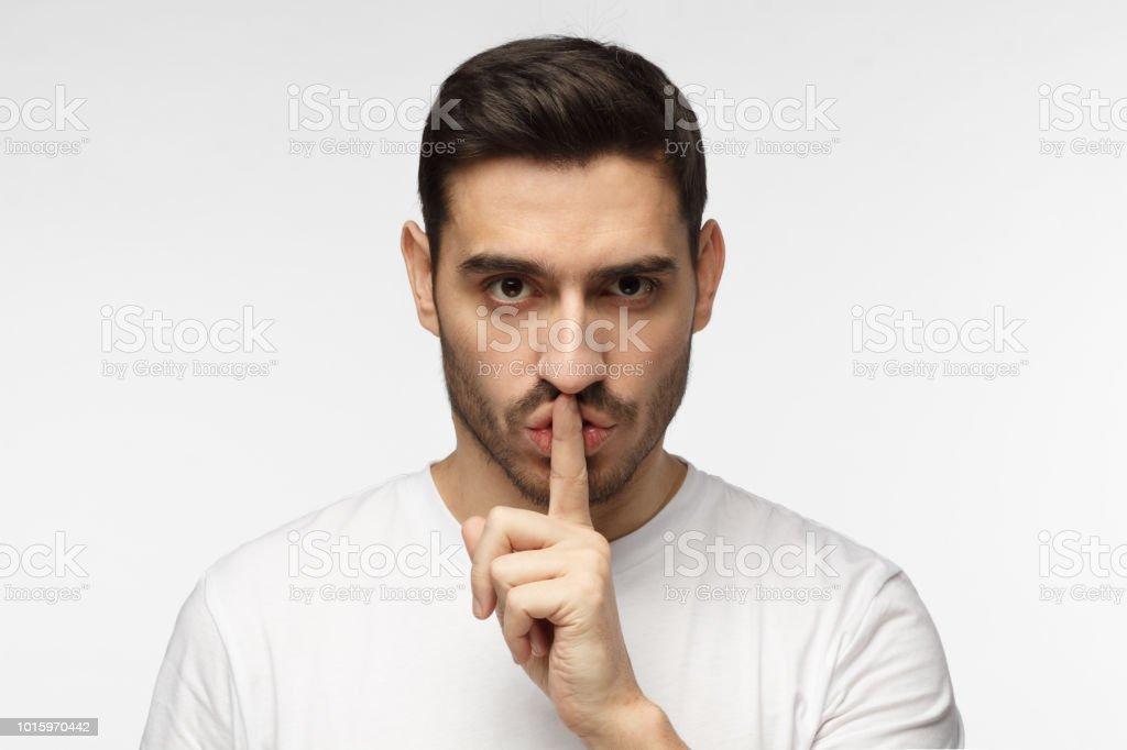 Cerrar tiro de guapo estricta con shh gesto, pidiendo silencio o a estar en silencio, aislado sobre fondo gris - foto de stock