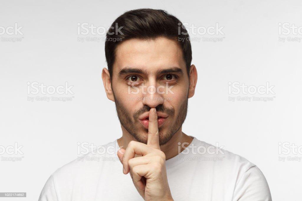 Cerrar tiro de guapo complicado con shh gesto, pidiendo silencio o a estar en silencio, aislado sobre fondo gris - foto de stock
