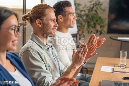 1141929391 istock photo Close up shot of happy group of businesspeople clapping in office. Young business partners applauding to reporter after listening to presentation at coworking zone 1173451196