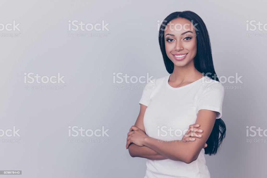 Close up shot of hot mixed raced brunette afro lady with crossed hands on pure grey backgrund, looking in the camera, She is in a casual white outfit, with natural daily cosmetics, long hairstyle stock photo