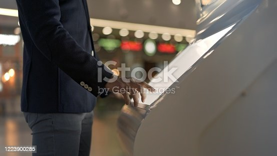 Young businessman hands dressed in jacket swiping for information in kiosk on background of lights of shopping mall. No face man with interactive wayfinding kiosk