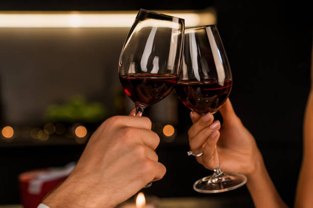 Close up shot of man and woman toasting and drinking red wine from glasses on dinner Couple, Romantic, Dinner, Togetherness, Holiday wine stock pictures, royalty-free photos & images