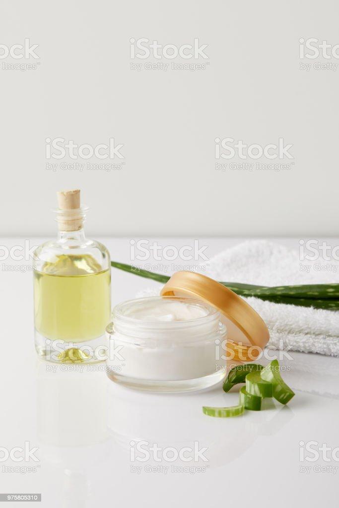Schuss von Bio Creme und Parfüm, Handtuch und Aloe Vera Scheiben Blatt auf weiße Fläche hautnah - Lizenzfrei Aloe Stock-Foto