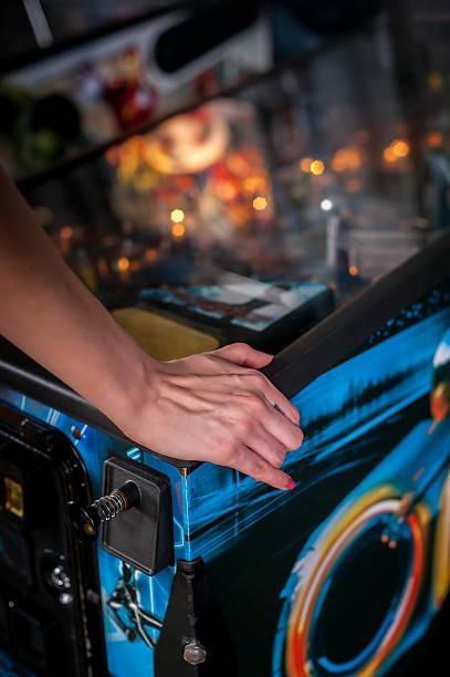 close up shot of person playing with a pinball machine - pinball spielen stock-fotos und bilder