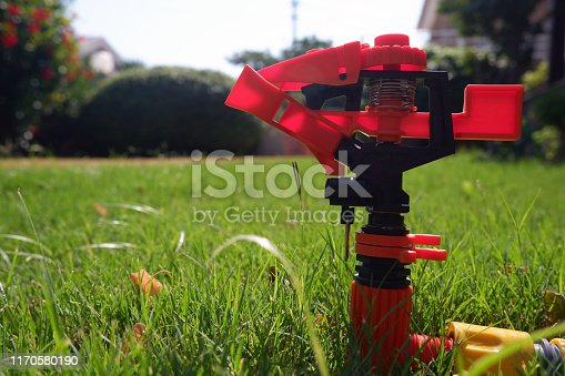 istock Close up shot of red and black sprinkler ready to spray water over green grass. 1170580190