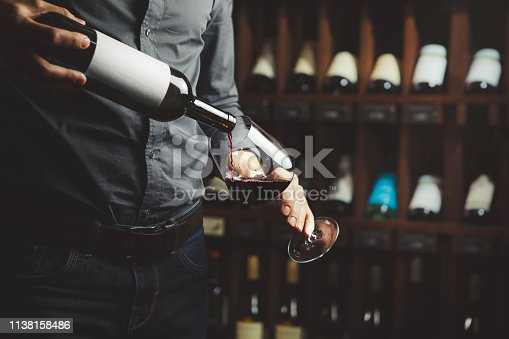 Sommelier male pouring red wine from bottle having label into glass on angle, alcoholic beverage degustation, cellar with containers and drinks set.