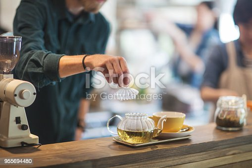 Close up shot of the hands of a cafe worker making tea