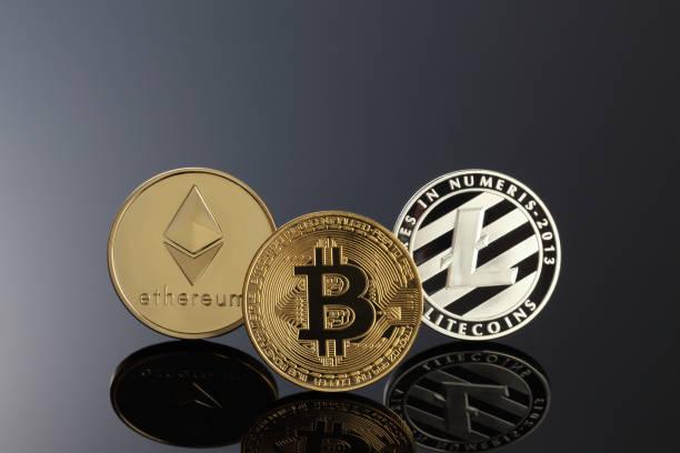 cerrar tiro de tres cryptocurrencies principales; bitcoin, etereum y litecoin en la superficie oscura. - criptomoneda fotografías e imágenes de stock
