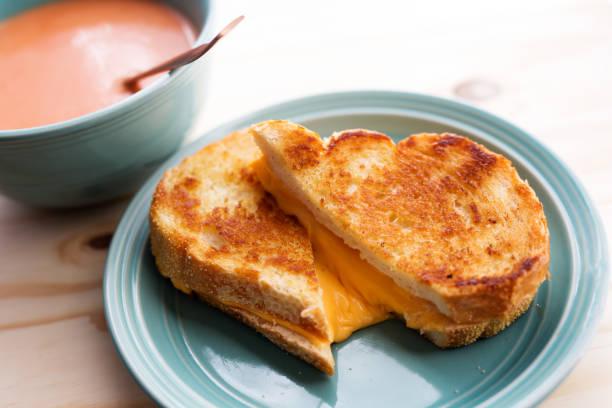 schuss von tomatensuppe mit einem käse-sandwich hautnah. blaue platte und hölzernen hintergrund. - kalte tomatensuppe stock-fotos und bilder