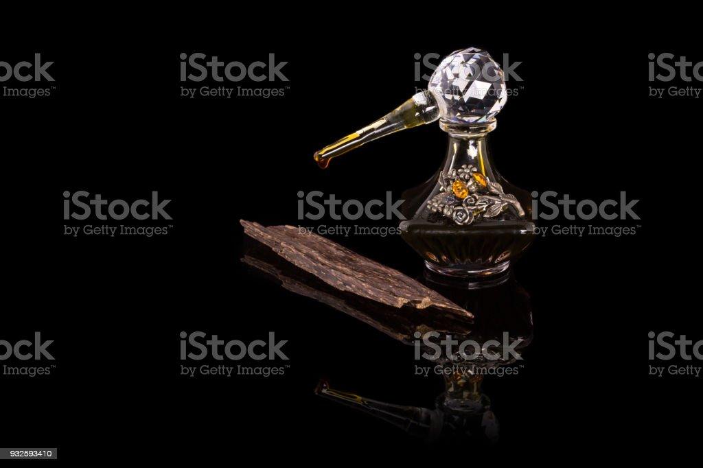 Étroite Up Shot de traditionnel luxe arabe Oud huile parfum dans A belle Handmade clair cristal verre Jar bouteille & verre compte-gouttes & Agar bois isolé sur fond Antique Style noir, espace de texte - Photo