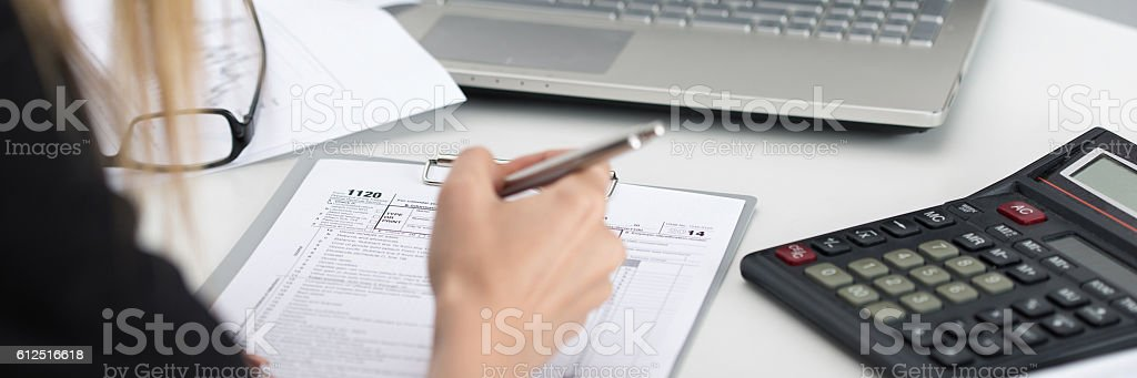 Close up shot of woman hand filling tax form stock photo