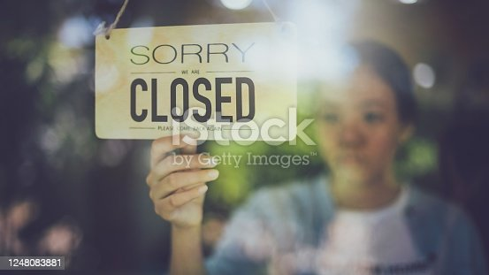 1213432934 istock photo Close up shot of woman hand turning close sign board on glass door in coffee shop and restaurant during coronavirus lockdown quarantine.Business crisis concept. 1248083881