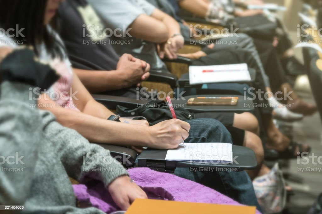 Close up shot of woman hand writing on the paper at the table in the conference hall or seminar meeting, business and education concept stock photo