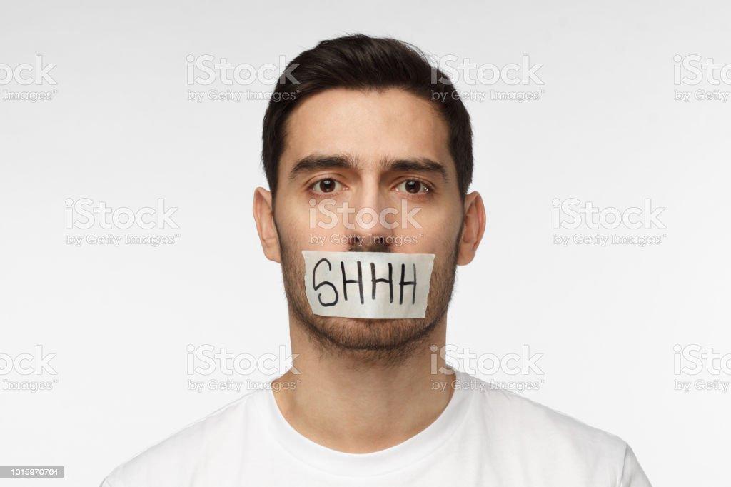 Foto de hombre joven con la boca encintada con shhh texto en él de cerca - foto de stock