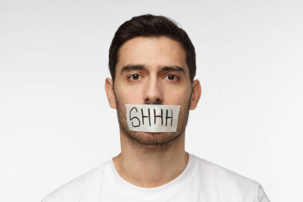 Close up shot of young man with taped mouth with shhh text on it Close up shot of young man with taped mouth with shhh text on it finger on lips stock pictures, royalty-free photos & images