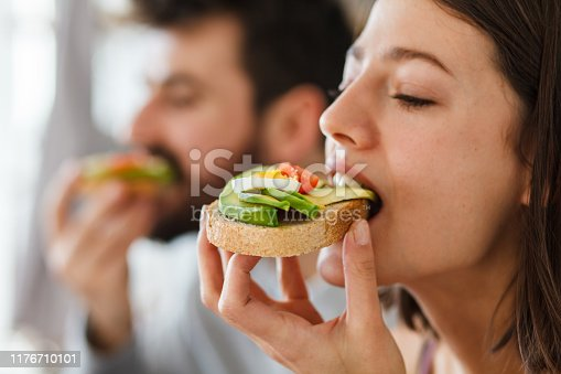 Close up shot of happy young woman biting into a delicious and healthy sandwich with avocado. She is enjoying breakfast in bed with her boyfriend.