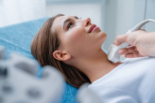 Close up shot of young woman getting her neck examined by doctor using ultrasound scanner at modern clinic Medicine, Hospital, Medical Clinic, Ultrasound, Doctor scientific imaging technique stock pictures, royalty-free photos & images