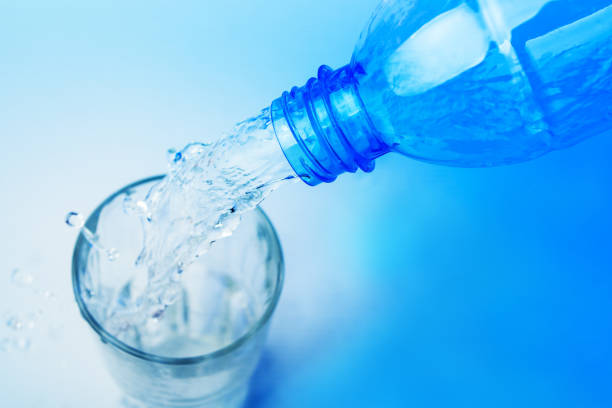 Close up shot : Pour water from plastic bottle in to the glass on blue backgroud stock photo