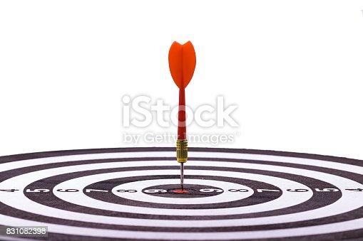 istock Close up shot red dart arrow on center of dartboard, metaphor to target success, winner concept 831082398