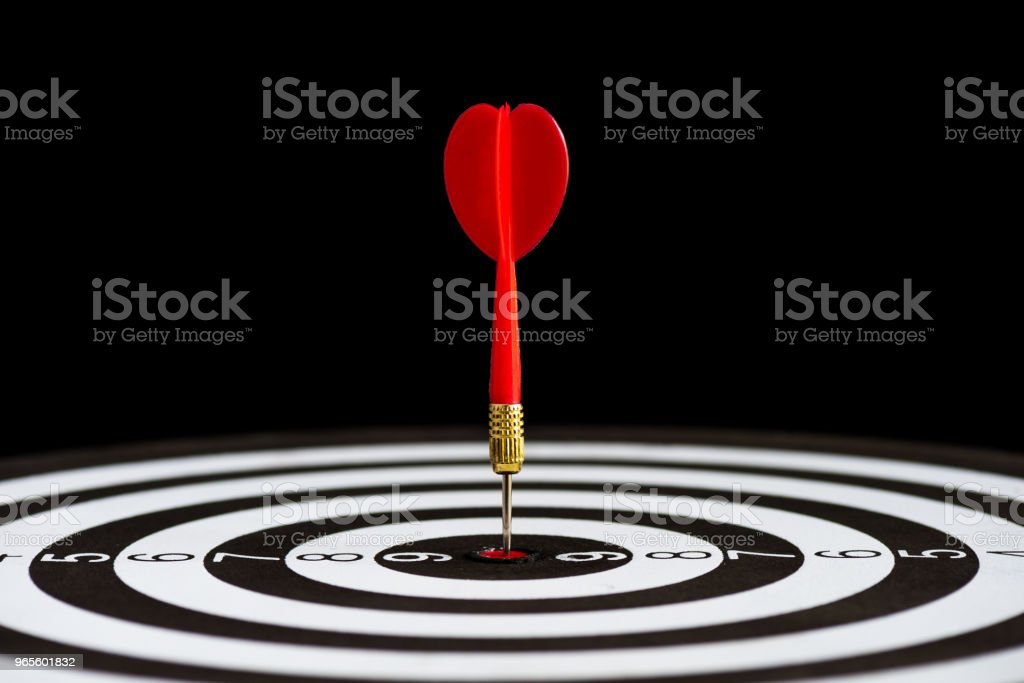 Close up shot red darts arrows in the target center on black background. Business target or goal success and winner concept. stock photo