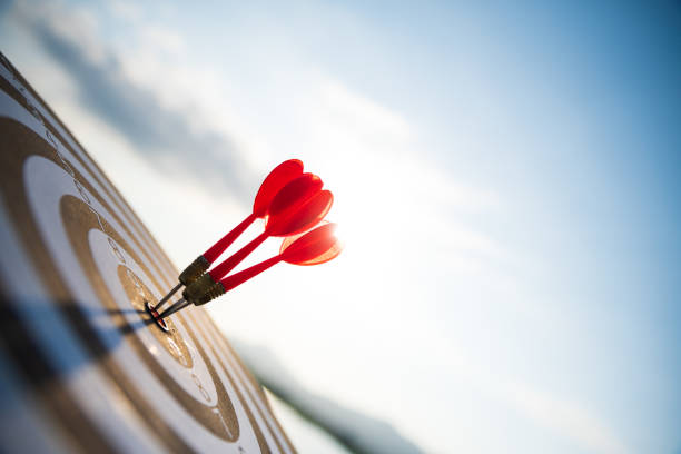 在深藍色的天空背景上,在目標中心特寫紅色飛鏢箭頭。業務目標或目標成功和贏家理念。 - 成功 個照片及圖片檔