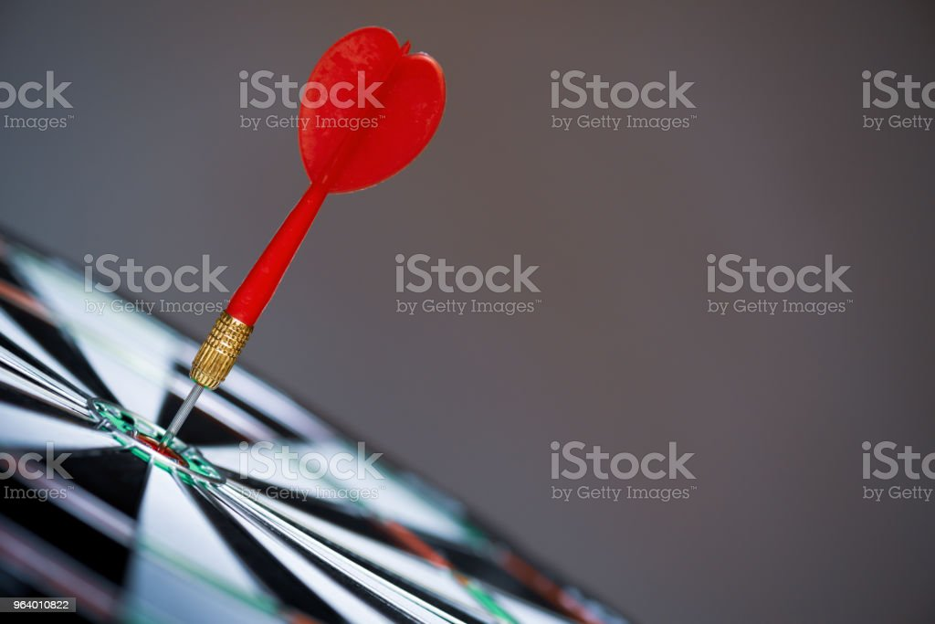 Close up shot red darts arrows in the target center on dark...