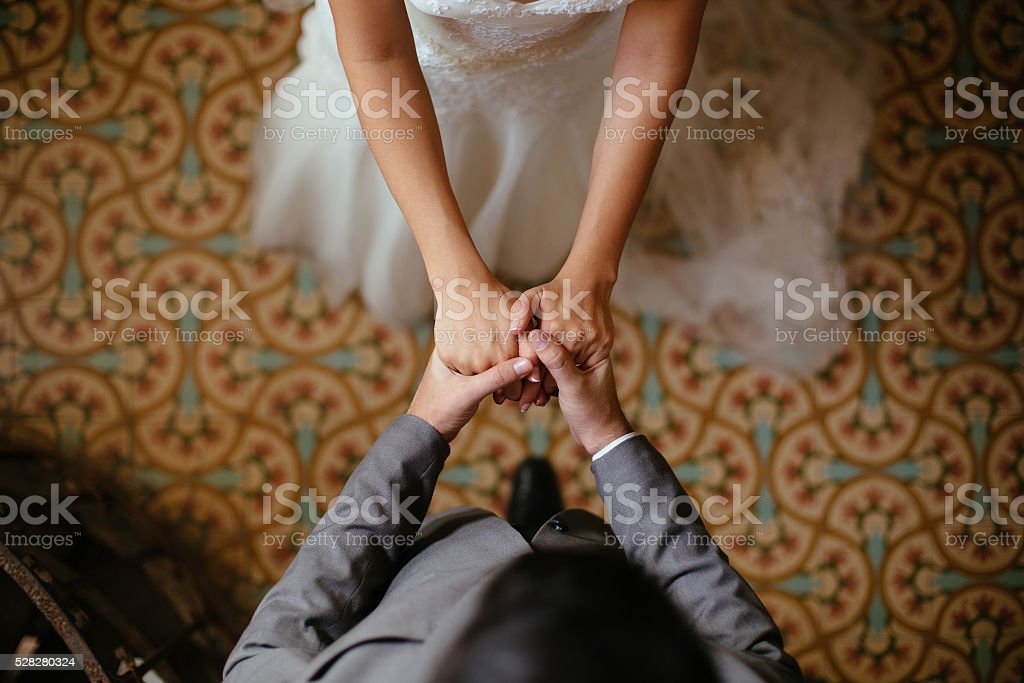 Close up shots of bride and groom holding hands stock photo