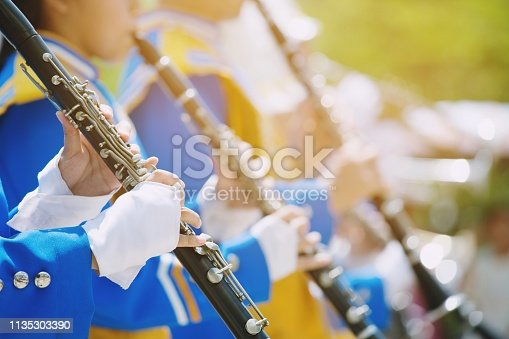 Close up show band parade and details of playing musicians instruments in a marching band performing playing a clarinet  woodwind Instruments.