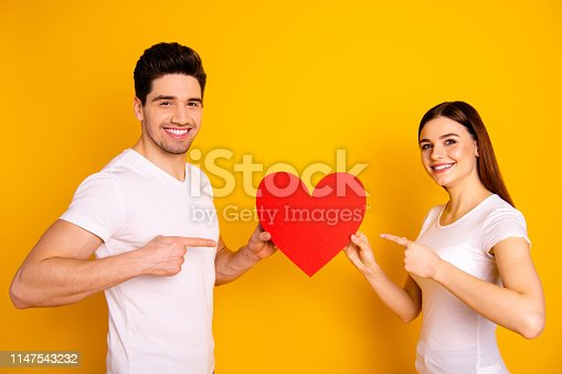 950598260 istock photo Close up side profile photo amazing beautiful she her he him his guy lady hold hands arms big paper heart shape figure postcard direct finger wear casual white t-shirts isolated yellow background 1147543232