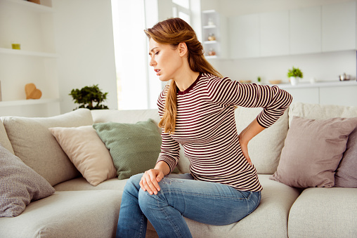 istock Close up side profile photo beautiful she her lady arms hands hold back spine suffering terrible pain wear jeans denim striped pullover clothes bright comfort flat house living room indoors 1147285589