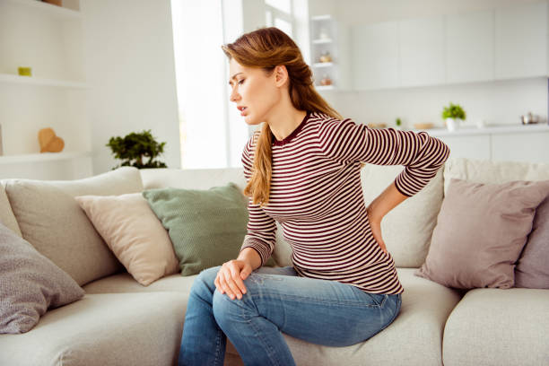 Close up side profile photo beautiful she her lady arms hands hold back spine suffering terrible pain wear jeans denim striped pullover clothes bright comfort flat house living room indoors Close up side profile photo beautiful she her lady arms hands hold back spine suffering terrible pain wear jeans denim striped pullover clothes bright comfort flat house living room indoors. back pain stock pictures, royalty-free photos & images