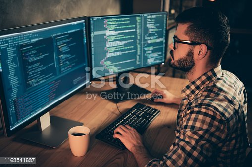 1170082013 istock photo Close up side profile photo handsome he him his guy brainstorming briefing coder typing php css keyboard development outsource IT two monitors table office agency wear specs formalwear plaid shirt 1163541637