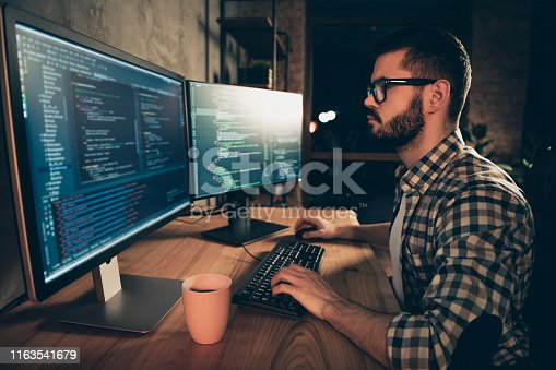 1170082013 istock photo Close up side profile photo handsome he him his guy brainstorming briefing coder typing php css keyboard development outsource IT two monitors table office agency wear specs formalwear plaid shirt 1163541679