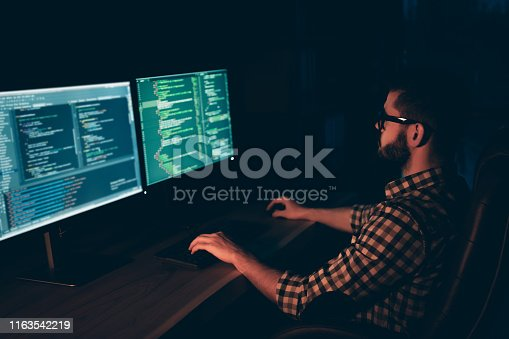 1170082013 istock photo Close up side profile photo handsome he him his guy coder typing keyboard development outsource IT processing language two monitors table office agency wear specs formalwear plaid shirt 1163542219