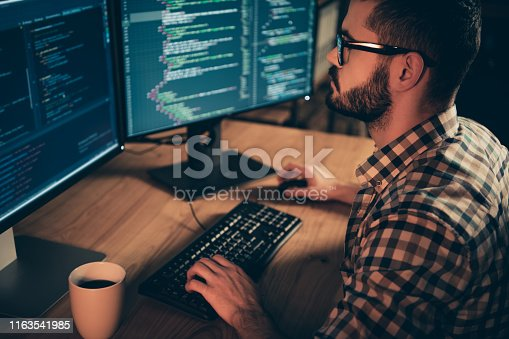 1170082013 istock photo Close up side profile photo handsome he him his guy linux windows cross platform coder typing php css keyboard development outsource IT monitors table office agency wear specs formalwear plaid shirt 1163541985