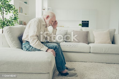 Close up side profile photo of grey haired he his him grandparent with chronic strong terrible ache head on hand illness wearing casual checkered shirt jeans denim outfit sitting comfy on divan